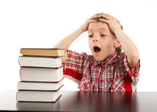 Shocked schoolboy looks at books Stock Images