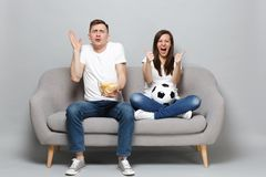 Shocked screaming couple woman man football fans cheer up support favorite team with soccer ball, holding bowl of chips royalty free stock image