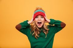 Shocked Screaming Young girl in sweater and hat holding head. Shocked Screaming Young girl in sweater and hat holding her head while looking at the camera over Stock Image