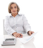 Shocked senior businesswoman looking at increasing costs. Royalty Free Stock Photo