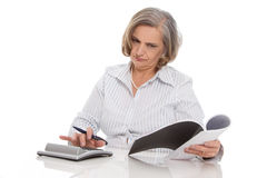 Shocked senior businesswoman looking at increasing costs. Stock Images