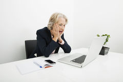 Shocked senior businesswoman using laptop at desk in office Royalty Free Stock Image