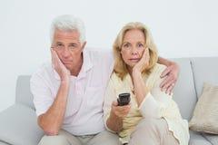 Shocked senior couple watching television Stock Photos