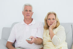 Shocked senior couple watching television Stock Photo