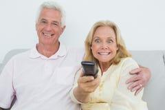 Shocked senior couple watching television Stock Images