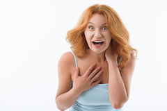 Shocked senior lady evincing her surprise. Excited middle-aged woman is looking at camera with shock and laughing. She is standing and raising hand to chest royalty free stock image
