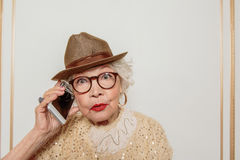 Shocked senior lady talking on smartphone. Who is this. Surprised old woman is answering the phone. She is standing and staring at camera with shock stock images