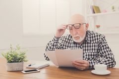 Shocked senior man looking at bills copy space. Shocked senior man looking at bills in disbelief, holding his glasses on forehead, copy space stock image