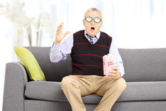 Shocked senior man with popcorn sitting on sofa and watching mov Stock Photography