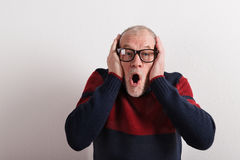 Shocked senior man in red and blue sweater, studio shot. Royalty Free Stock Photo