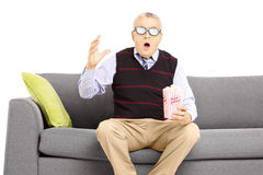 Shocked senior man sitting on a sofa and watching movie Stock Photos
