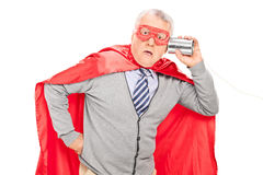Shocked senior superhero with a tin can phone. Isolated on white background Royalty Free Stock Photography
