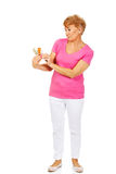 Shocked senior woman holding few tablets package.  stock photo