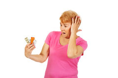 Shocked senior woman holding few tablets package.  royalty free stock image