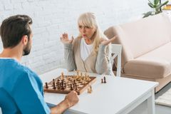 Shocked senior woman playing chess with young. Social worker royalty free stock photo