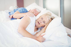 Shocked senior woman sleeping besides man on bed Royalty Free Stock Photography