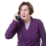 Shocked senior woman on telephone Stock Image
