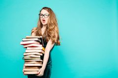 Shocked teacher holding many books and screaming. Portrait of emotionally shocked teacher in dress with lace, eyeglasses, holding many books and surprised royalty free stock images