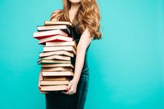 Shocked teacher holding many books and screaming. Portrait of emotionally shocked teacher in dress with lace, eyeglasses, holding many books and surprised stock photo