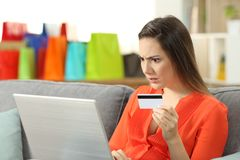 Shocked shopper buying online with credit card. Sitting on a couch in the living room at home stock photos