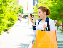 Shocked shopper woman looking at her smart phone Stock Photography