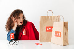 Shocked shopping sale woman sitting with paper shopping bags. Isolated over white background Royalty Free Stock Photography