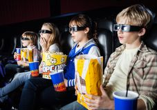 Shocked Siblings Watching 3D Movie In Theater. Shocked siblings having snacks while watching 3D movie in cinema theater Royalty Free Stock Images