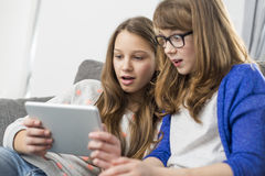 Shocked sisters using digital tablet on sofa at home Stock Photos