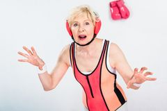 Shocked sportive senior woman looking at camera while training. On grey royalty free stock photo