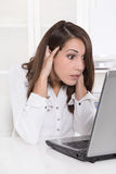 Shocked and stressed business woman at desk with her computer - Stock Photo