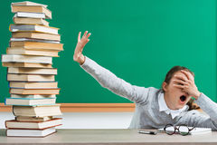 Shocked student closes her eyes to a lot of books. Stock Image
