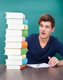 Shocked student looking at books. Portrait Of A Shocked Male Student Looking At Stack Of Books Stock Photo