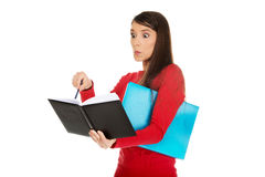 Shocked student woman with her note. Royalty Free Stock Image