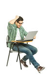 A shocked student working on a laptop. A shocked student sitting on a chair and working on a laptop on white background Stock Photography