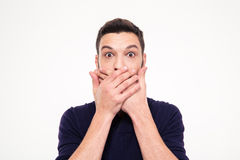 Shocked stunned young man covered mouth by hands. Over white background Royalty Free Stock Image