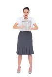 Shocked stylish businesswoman holding newspaper Stock Photo