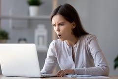 Shocked subrayó a la mujer que miraba sorpresa negativa de lectura del ordenador portátil en línea fotografía de archivo