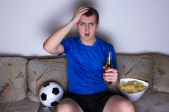 Shocked supporter in uniform sitting on the sofa and watching fo Royalty Free Stock Photos