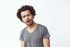 Shocked surprised african man looking at camera over white background. Copy space. Royalty Free Stock Photos