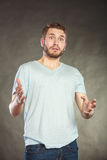Shocked surprised amazed handsome man guy. Portrait of shocked surprised amazed handsome man in shirt. Young guy posing in studio on black Stock Photo