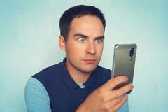 Shocked and surprised asian man looking smartphone. Amazed young guy reads a message on the phone. stock photography
