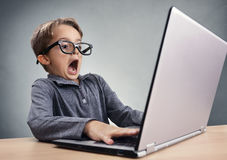 Shocked and surprised boy on the internet with laptop computer Royalty Free Stock Photos
