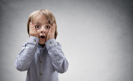 Shocked and surprised child. Shocked and surprised boy with copy space concept for amazement, astonishment, making a mistake, stunned and speechless or back to Stock Image