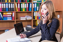 Shocked surprised woman talking on phone in office. Surprised woman talking on phone in office Royalty Free Stock Photo