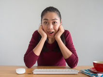 Shocked and surprised woman working on her desk. Royalty Free Stock Images