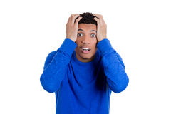 Shocked and surprised young placing hands on head in disbelief Stock Photography
