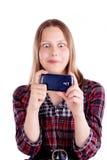 Shocked teen girl looking at mobile phone screen. Studio shot Royalty Free Stock Image