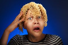 Shocked teen girl with macaroni instead hair Royalty Free Stock Photography