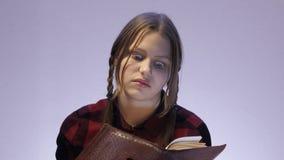 Shocked teen girl reading book. 4K UHD stock video footage