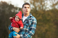 Shocked Teenage Boy Holding Baby. In park Stock Image